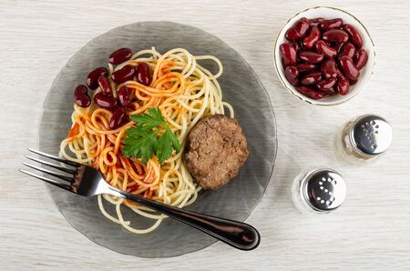 Fork in grey glass plate with spaghetti, chicken cutlet, beans, leaf of parsley, bowl with red beans, salt shaker, pepper shaker on light wooden table. Top view