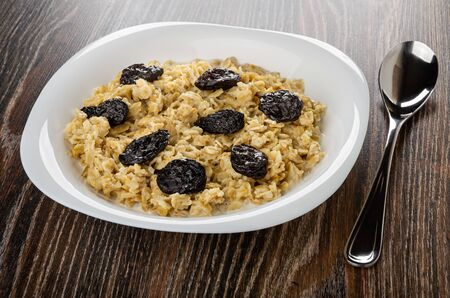 Dairy oatmeal porridge with prunes in white glass plate, spoon on dark wooden table