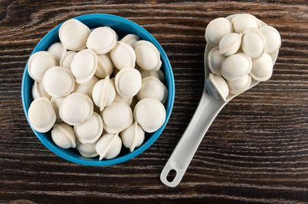 Raw frozen small dumplings in blue glass bowl, dumplings in plastic spoon on dark wooden table. Top view Banco de Imagens - 134823852