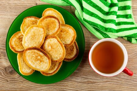 Fried homemade pancakes in green plate, striped napkin, cup with tea on wooden table. Top view