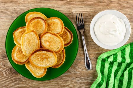 Fried homemade pancakes in green plate, fork, bowl with sour cream, striped napkin on wooden table. Top view Banco de Imagens - 134824097