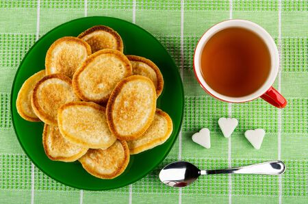 Fried homemade pancakes in glass plate, cup with tea, figured pieces of sugar, teaspoon on green checkered tablecloth. Top view