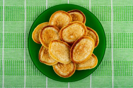 Fried homemade pancakes in glass plate on green checkered tablecloth. Top view Banco de Imagens