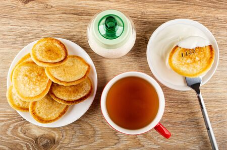 Plate with fried pancakes, sugar bowl, pancake in sour cream strung on fork above white bowl, cup of tea on wooden table. Top view Banco de Imagens