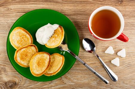 Fried pancakes, pancake in sour cream strung on fork in green plate, cup of tea, pieces of sugar, teaspoon on wooden table. Top view