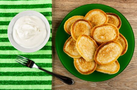 Bowl with sour cream, fork on striped napkin, fried homemade pancakes in green plate on wooden table. Top view