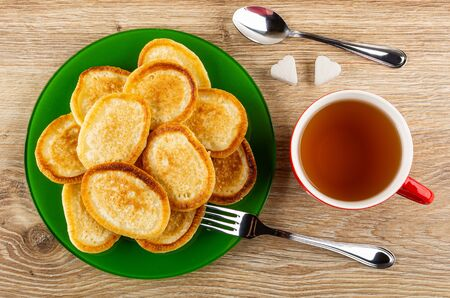 Fried homemade pancakes in green plate, figured pieces of sugar, teaspoon, cup with tea, fork on wooden table. Top view Banco de Imagens - 134824106