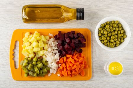 Chopped potatoes, beetroot, raw onion, gherkins, carrots on cutting board, canned green peas in bowl, salt shaker, bottle of vegetable oil for vinaigrette on wooden table. Top view