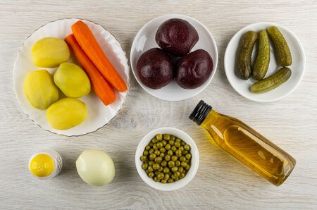 Boiled potatoes, carrots, beetroot, canned green peas, gherkins, raw onion, salt shaker, bottle of vegetable oil for cooking vinaigrette on wooden table. Top view