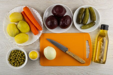 Boiled potatoes, carrots, beetroot, canned green peas, gherkins, onion and kitchen knife on cutting board, salt shaker, bottle of vegetable oil for vinaigrette on wooden table. Top view Banco de Imagens