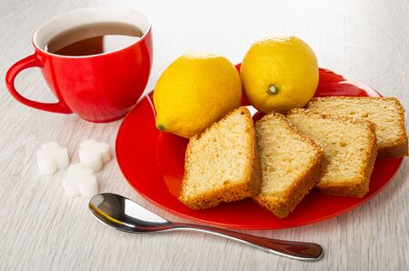 Cup of tea, pieces of sugar, red plate with yellow lemons, pieces of muffin, teaspoon on wooden table