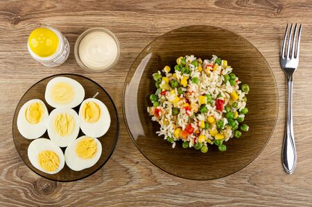 Salt shaker and bowl with mayonnaise, brown glass saucer with halves boiled eggs, plate with vegetable mix, fork on wooden table. Top view
