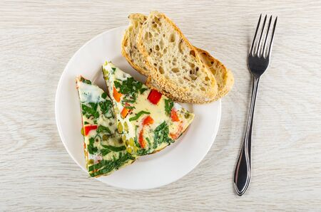 Pieces of omelet with spinach, sweet pepper, green peas in white plate, fork on wooden table. Top view