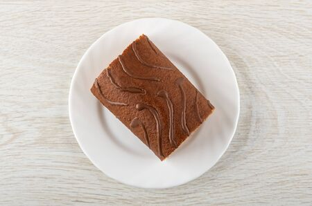Piece of chocolate roll in white plate on wooden table. Top view Banque d'images