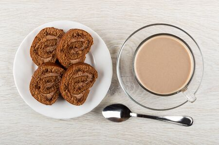 Slices of brown swiss roll in white plate, teaspoon, cup of cocoa with milk on saucer on wooden table. Top view Banque d'images