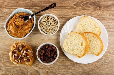 Spoon in blue glass bowl with peanut butter, sandwich with peanut pasta, bowls with sunflower seeds and raisin, slices of bread in white plate on wooden table. Top view