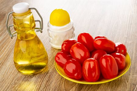 Salt shaker, transparent bottle with vegetable oil, yellow plate with red tomato cherry on brown wooden table