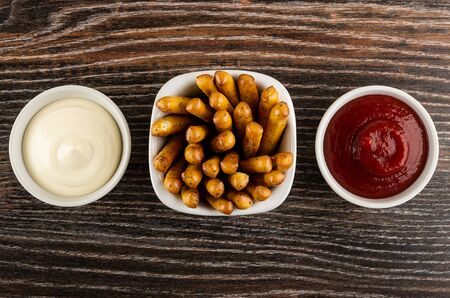 White bowls with mayonnaise, breadsticks and ketchup on dark wooden table. Top view Zdjęcie Seryjne