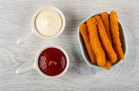 Mayonnaise and ketchup in sauce bots, fried breaded chicken sticks in bowl on wooden table. Top view Stock fotó
