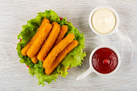Heap of fried breaded chicken sticks on leaves of lettuce in saucer, mayonnaise and ketchup in sauce bots on wooden table. Top view