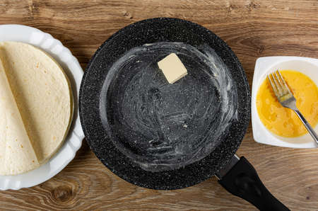 Few wheat tortilla in white dish, frying pan greased butter, fork in white bowl with mixed raw eggs on wooden table. Top view