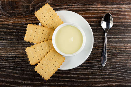 Few dry cookies and small white bowl with condensed milk in glass saucer, spoon on dark wooden table. Top view