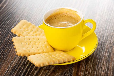 Few dry cookies, cup with coffee espresso on yellow saucer on dark wooden table