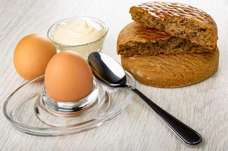 Transparent bowl with mayonnaise, rye breads, brown egg on glass egg stand, teaspoon on wooden table Imagens