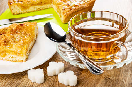 Kitchen knife, sweet lemon pie on green cutting board, piece of pie in white plate, cup of tea, teaspoon on saucer, sugar cubes on wooden table Stock fotó