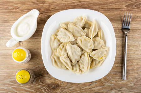 Sauce boat with sour cream, salt and pepper shakers, boiled dumplings with butter in white glass plate, fork on brown wooden table. Top view