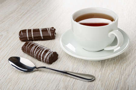 Striped marshmallows in chocolate, teaspoon, cup of tea on saucer on wooden table
