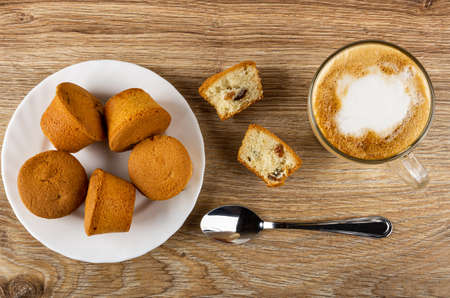 Small muffins in white plate, halves of muffin, teaspoon, cappuccino in transparent glass cup on brown wooden table. Top view