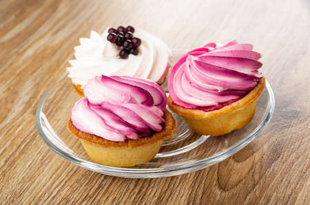 Tartlets with pink and white buttercream in transparent glass saucer on wooden table