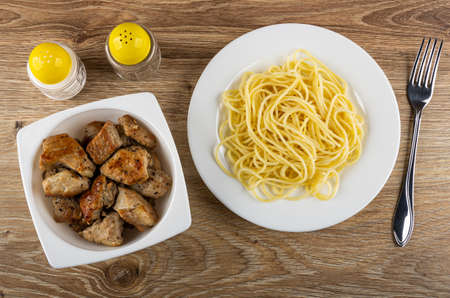 Pepper and salt shakers, glass white bowl with pieces fried pork meat, plate with spaghetti, fork on wooden table. Top view Standard-Bild