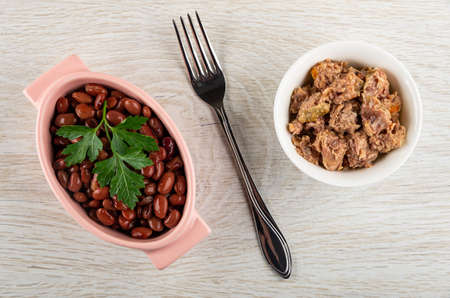 Pink bowl with canned red beans and leaf of parsley, fork, bowl with chicken stew on light wooden table. Top view