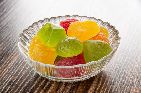 Multi-colored marmalade of different shapes in transparent glass bowl on dark wooden table