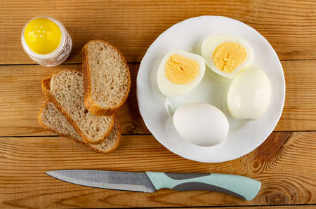 Salt shaker, slices of bread, glass plate with whole eggs and halves of boiled egg, kitchen knife on wooden table. Top view