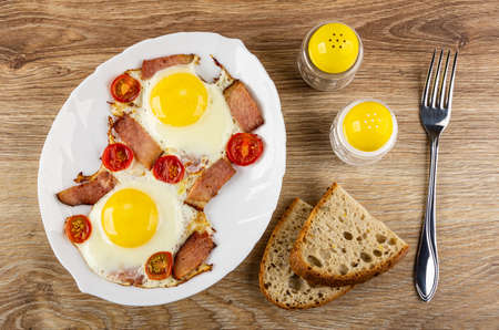Fried eggs with slices of gammon and cherry tomato in white dish, salt and pepper shakers, pieces of bread, fork on wooden table. Top view Stock fotó
