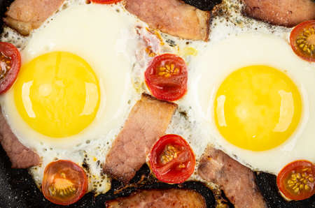 Fried eggs with gammon and tomato cherry. Top view