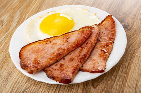 Fried egg and slices of fried gammon in white plate on wooden table