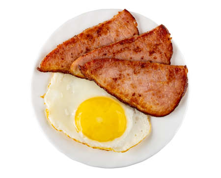 Fried egg and slices of fried gammon in glass plate isolated on white background. Top view