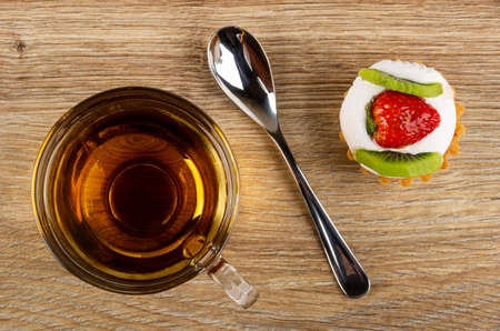 Transparent cup with tea, teaspoon, tartlet with cream, strawberry and kiwi on wooden table. Top view