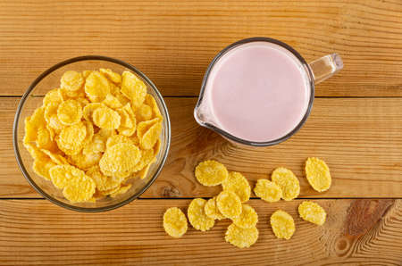 Corn flakes in glass transparent bowl, pitcher with pink fruit yogurt, scattered cornflakes on wooden table. Top view