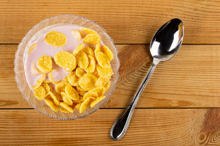 Transparent glass bowl with cornflakes and pink fruit yogurt, metallic spoon on wooden table. Top view