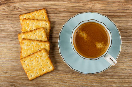 Few crunchy cookies with sesame, coffee espresso in light-blue cup on saucer on wooden table. Top view Stock fotó