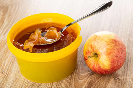 Spoon in apple marmalade in yellow plastic jar, red striped apple on brown wooden table