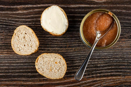 Slices of wheat bread, sandwich with butter, teaspoon in opened jar with pollock roe on dark wooden table. Top view