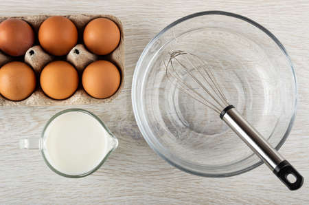 Cardboard box with brown chicken eggs, jug of milk, whisk in transparent bowl on wooden table. Top view