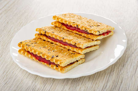 Sandwiches from crackers with flax seeds and cherry jam in white plate on wooden table