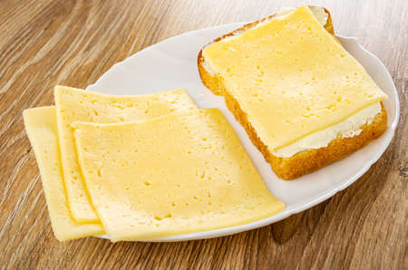Few thin slices of cheese, sandwich with butter and cheese in white dish on wooden table